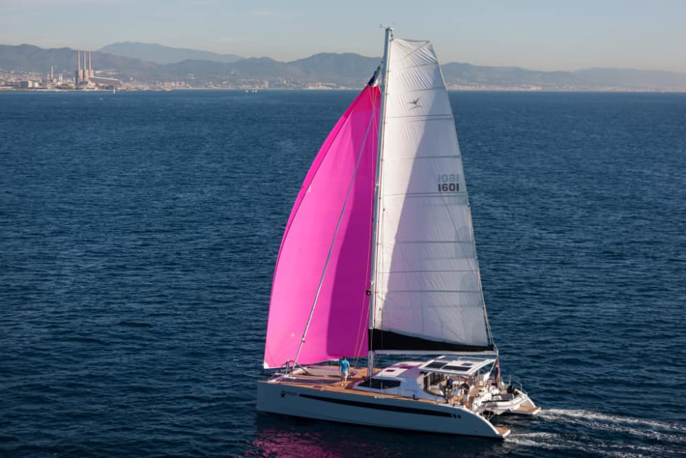 seawind 1600 sailing catamaran with a bright pink headsail