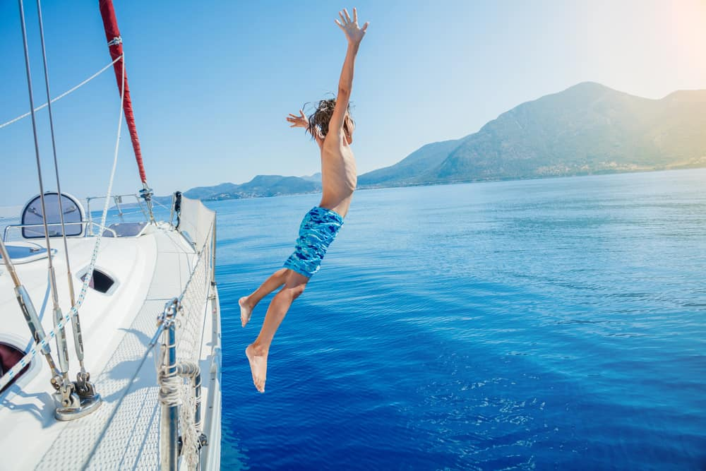 boy jumping off a sailboat into the water