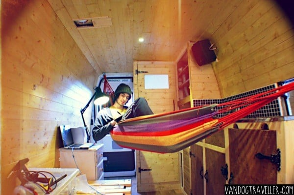 Man in a hammock inside his campervan interior