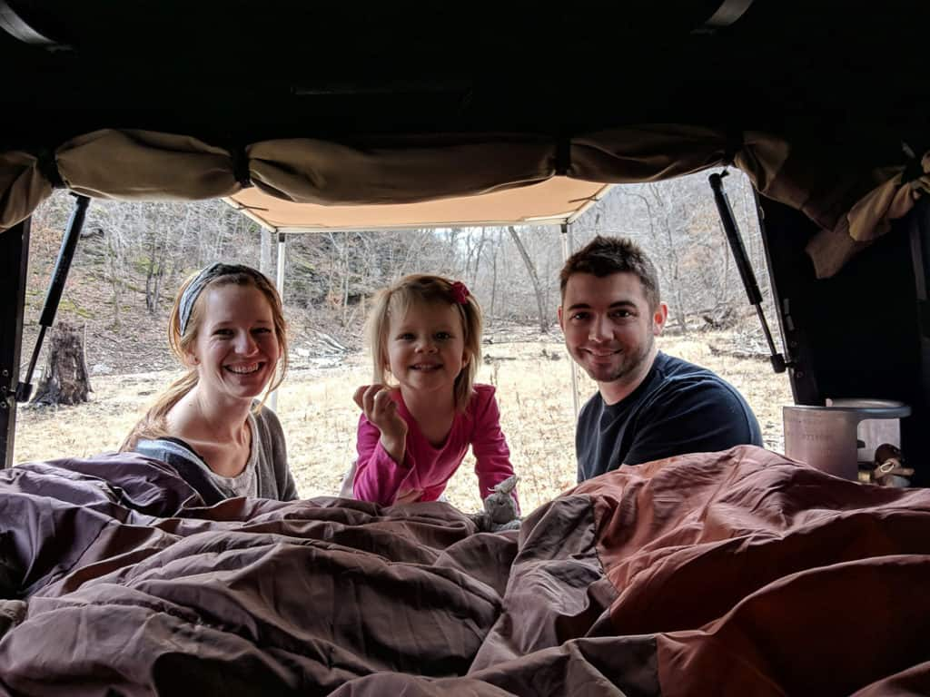 Family of three smiling in the back of their DIY truck camper