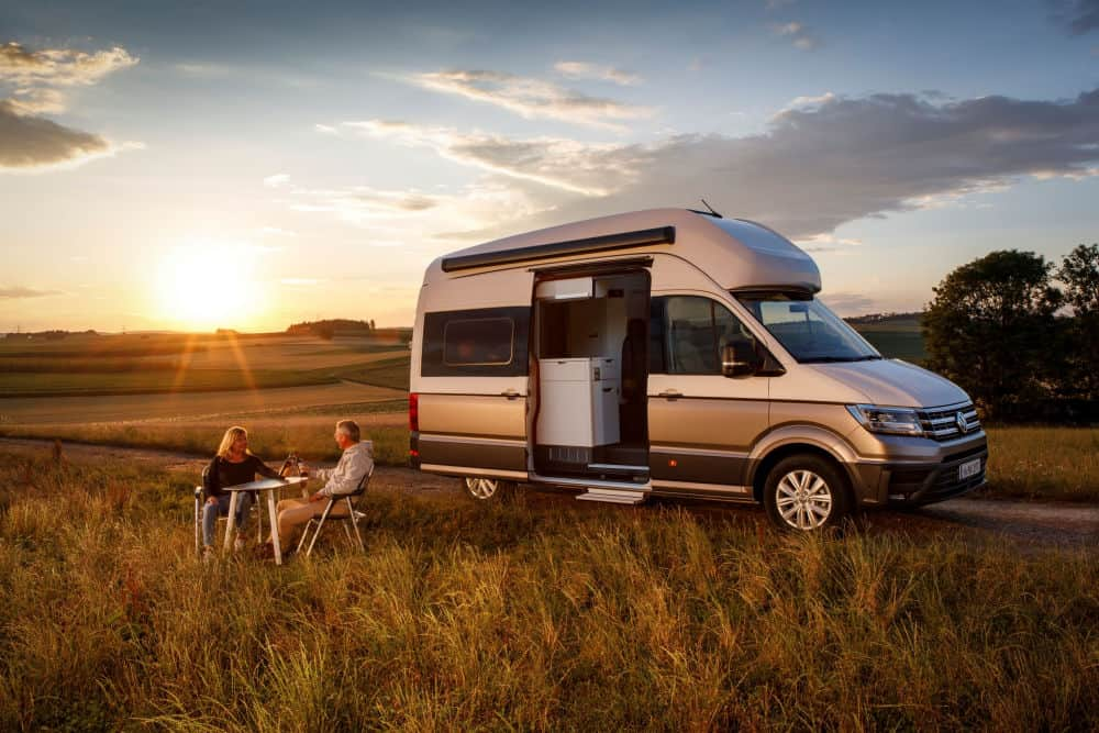 The VW Grand California Camper Van parked in a meadow at sunset