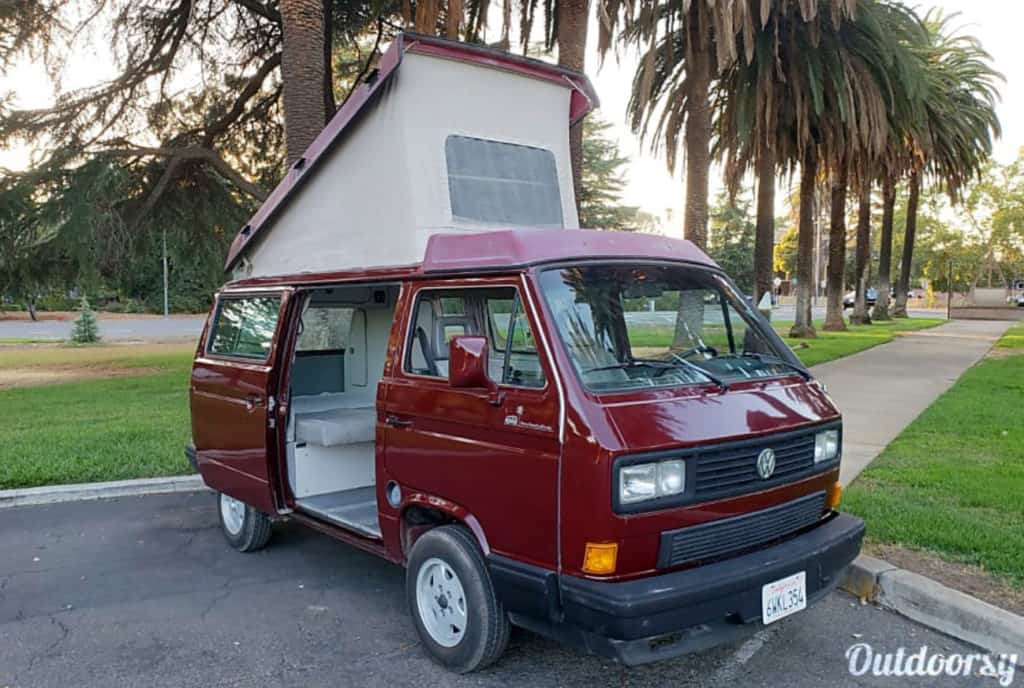 Maroon VW Vanagon with pop topped and side door open