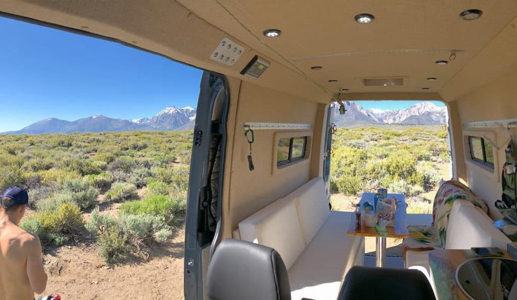 The campervan interior of a large Sprinter van with dinette and two couches