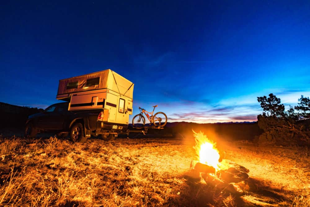 Four Wheel Truck camper outdoors at night by a fire