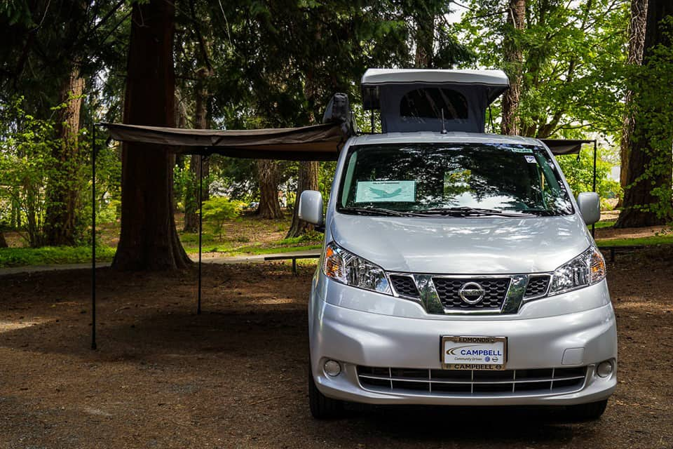 Nissan NV200 camper parked with the pop-top up and an awning extended