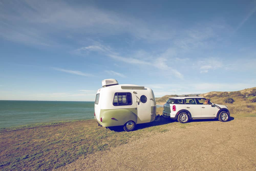 Small car towing a Happier Camper on the beach