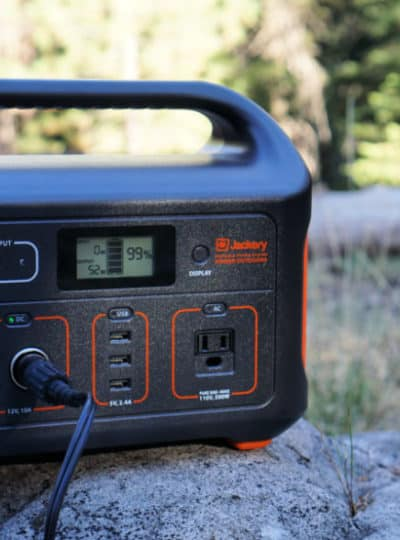 Jackery Explorer 500 turned on sitting on a rock in a campground