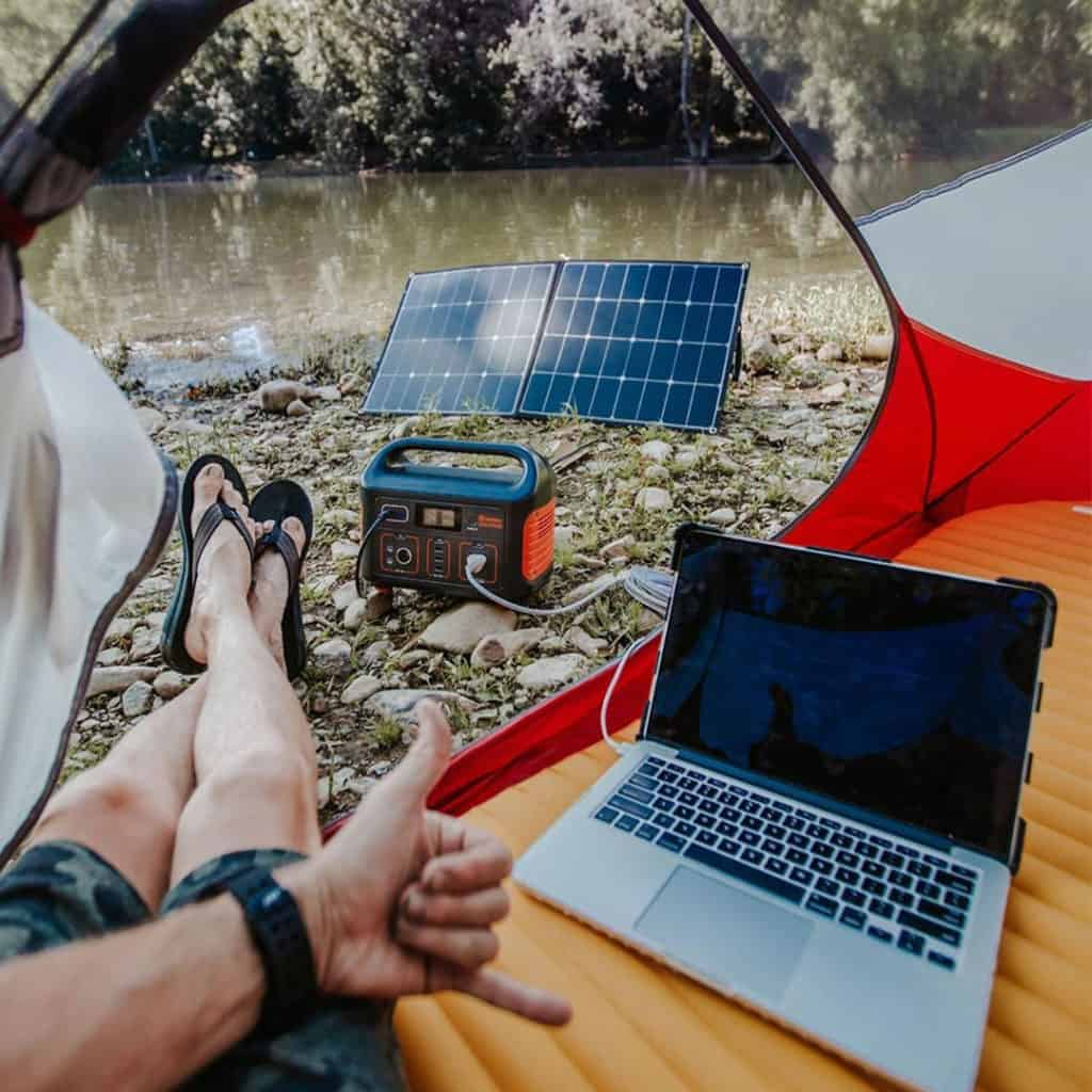 Person using a computer connected to a Jackery Explorer 500 for camping
