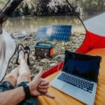 Person using a computer connected to a portable power station for camping