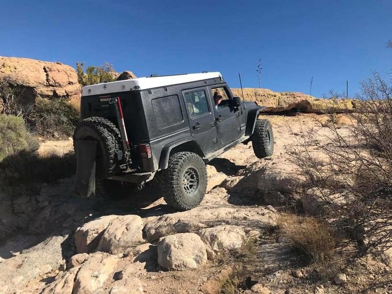 Black Jeep camper driving over rocks in the desert