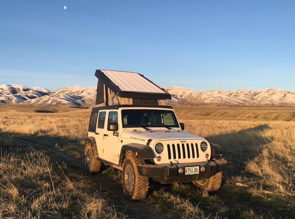 Pop up jeep camper parked with mountains in the background