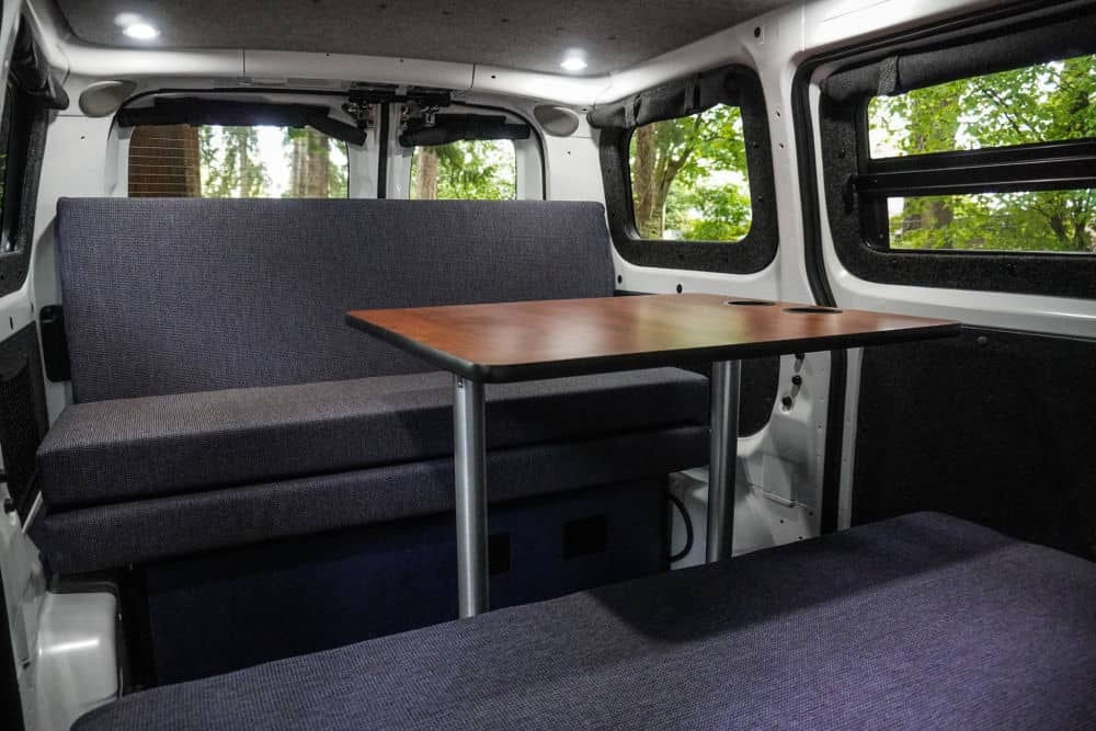 The sitting area complete with a table in the Free Bird Nissan camper