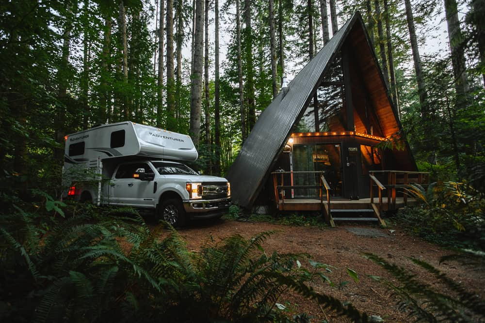 A truck camper (the adventurer) on the back of a pickup truck next to an A Frame house in the forest