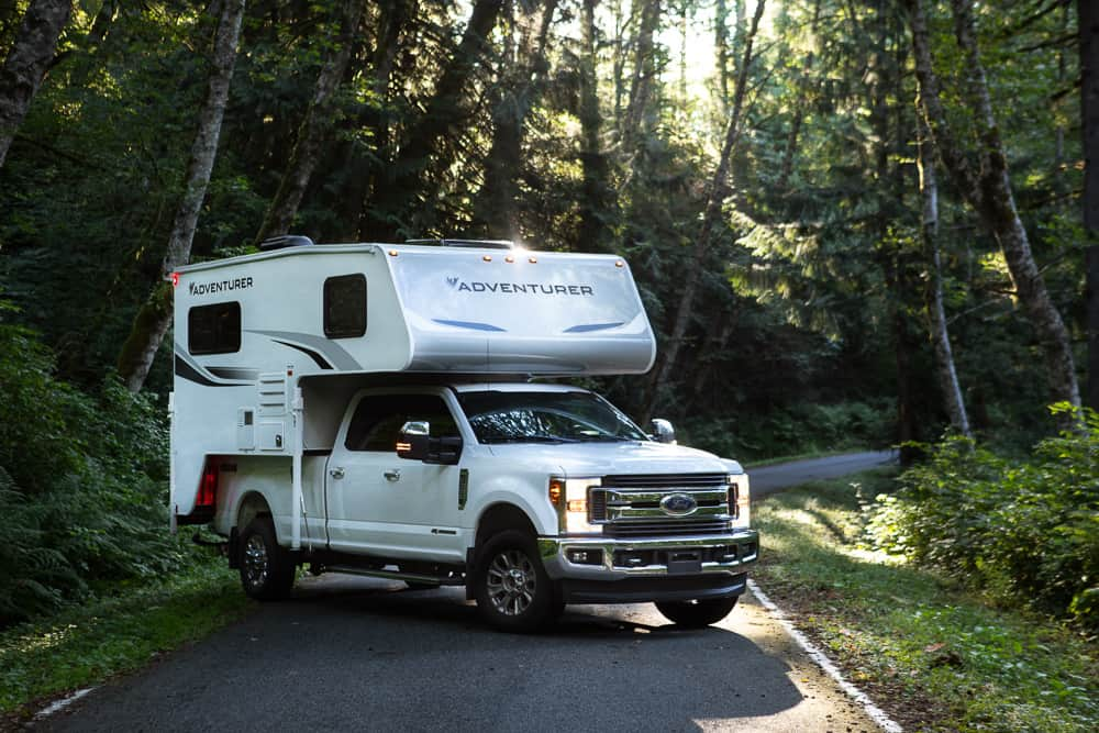 The Adventurer Truck Camper mounted on a pickup truck on a forest road