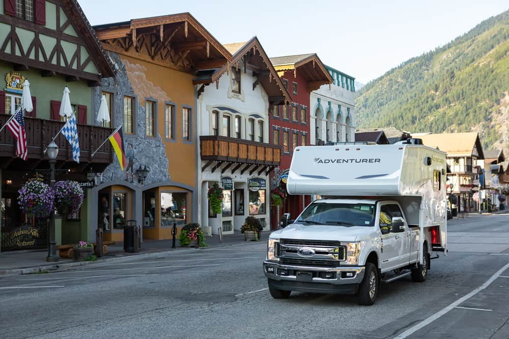 Truck with truck camper (Adventurer 910DB) driving through a mountain town