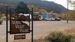 Sign for Animas Valley Village with tiny homes parked behind it