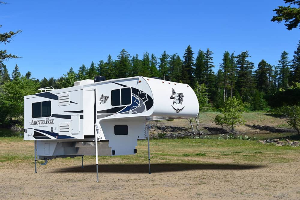The Arctic Fox 1150 truck camper made by Northwoods, with no pick up truck attached. The photo shows how this truck bed camper can be stored off of a vehicle