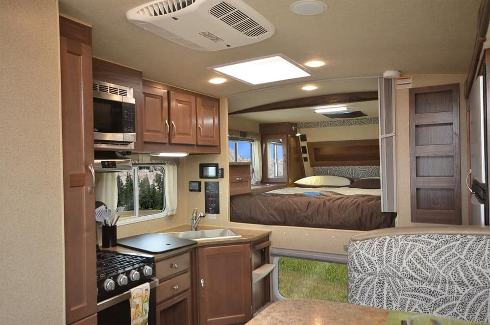 Spacious interior of a truck camper made by Northwood. The interior of the Arctic Fox 1150 features a bed, dinette, kitchen and dry bathroom.