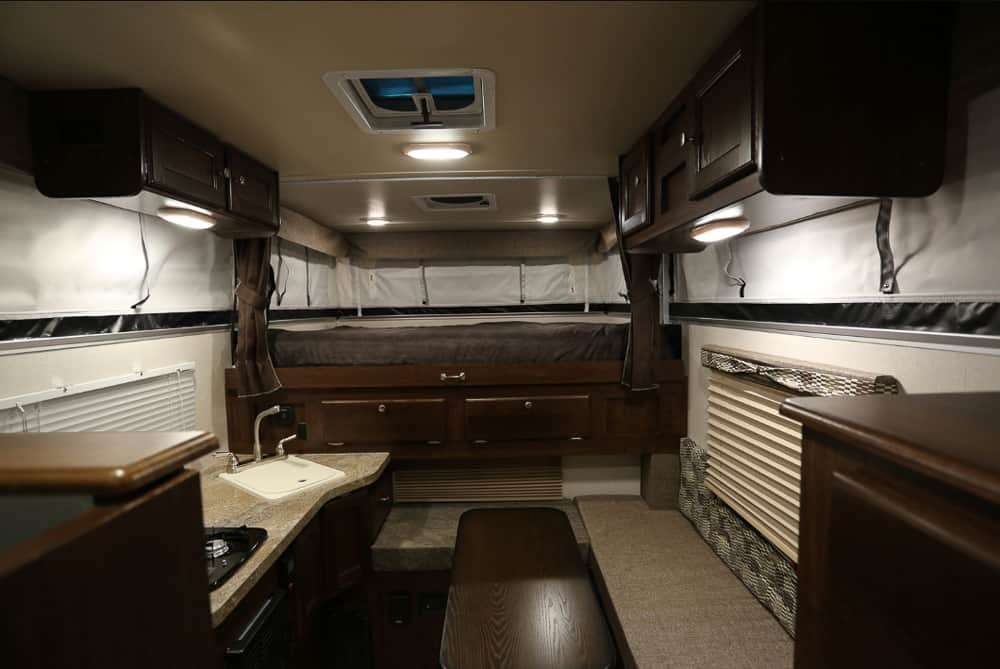 Interior of the explore backpack truck camper SS-1500 model, featuring dark wood accents, a bed and seating area