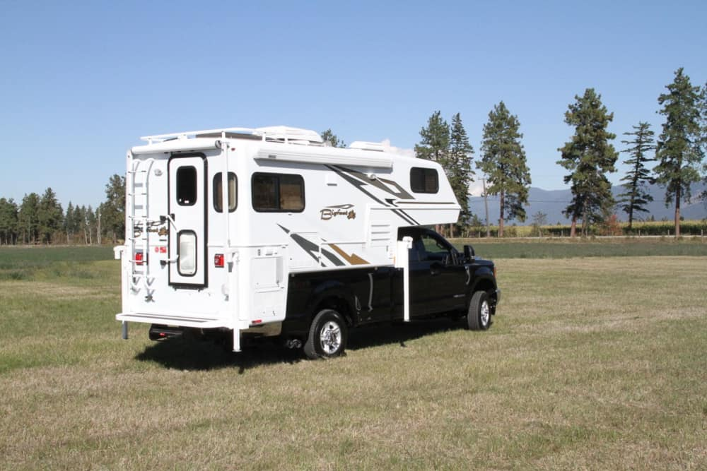large white truck bed camper on a black pickup truck in a field. The camper model is the Bigfoot RV 25C10.6E