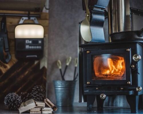 cubic mini rv wood stove burning in a camper