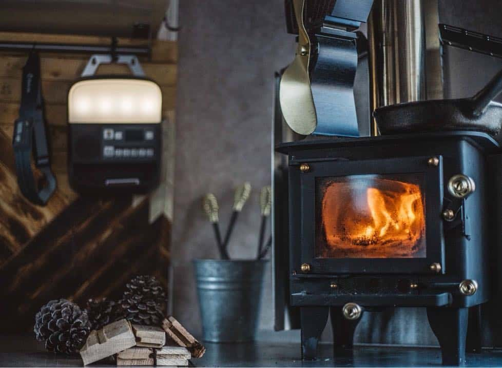 cubic mini rv wood stove burning in a camper