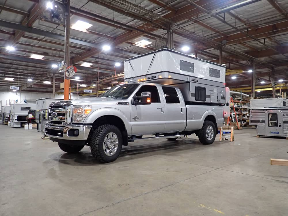 A pop up truck bed camper sitting in a truck bed in the Four Wheel Campers warehouse.