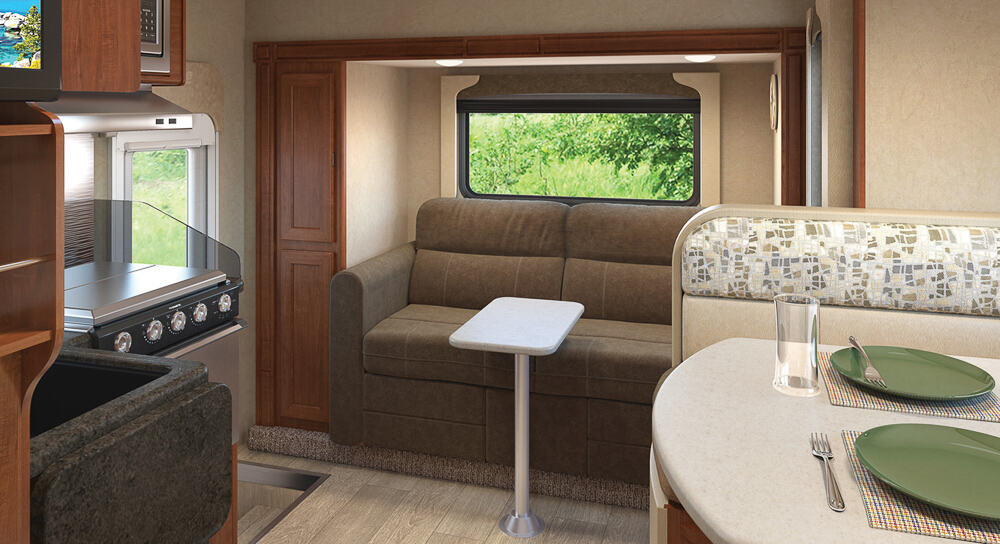 Interior of the Lance 1172 Truck Bed Camper, featuring a kitchen, dinette and a couch with a small table.