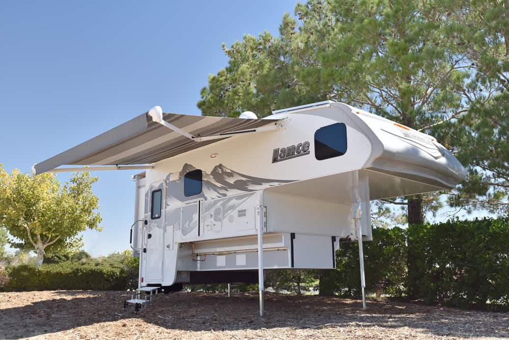 White truck bed camper, free-standing without truck underneath. Truck camper model is the Lance 1172