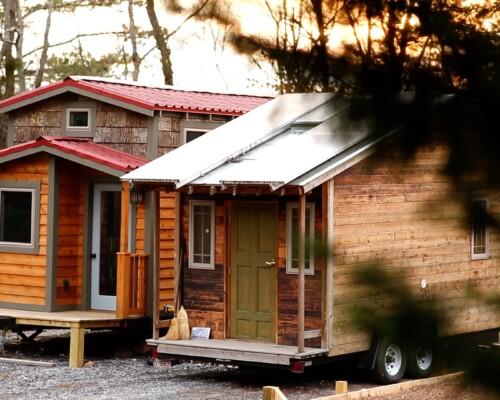 two tiny houses parked next to each other in a tiny house community