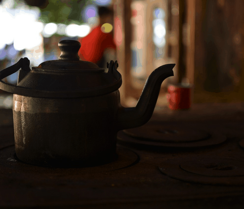 A cast iron teapot on top of an RV wood stove.