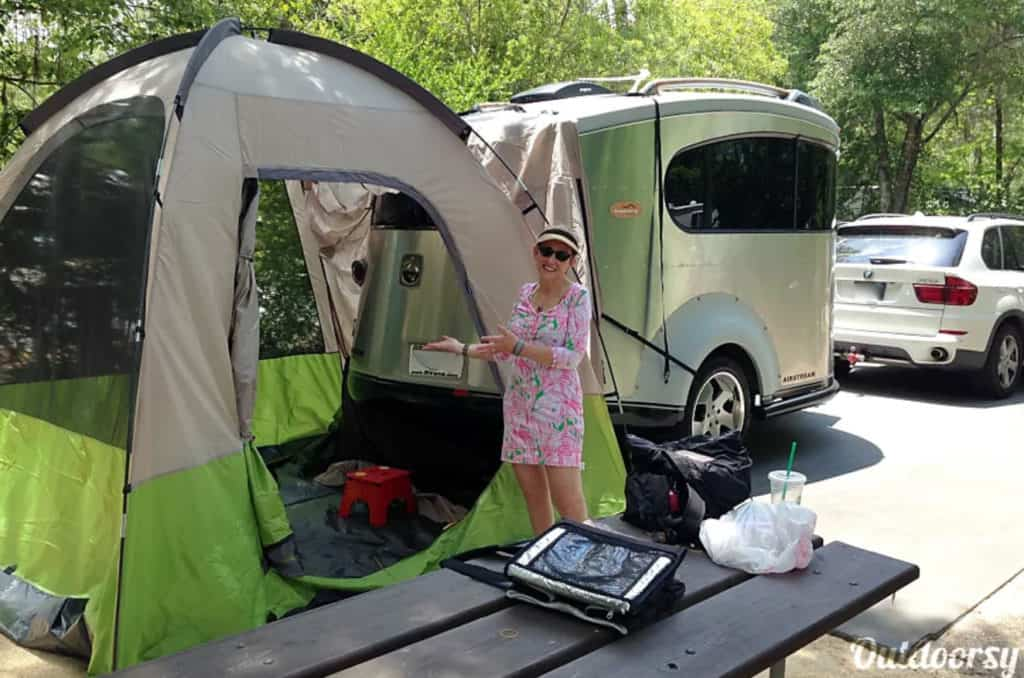 Woman standing near a tent outside an Airstream trailer rental