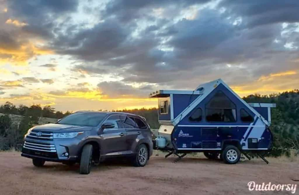Car hauling an A liner camping trailer rental outdoors