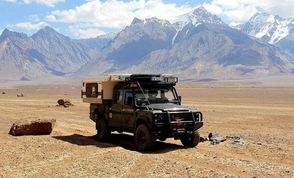 A Land Rover Defender and pop up truck camper in Tajikistan