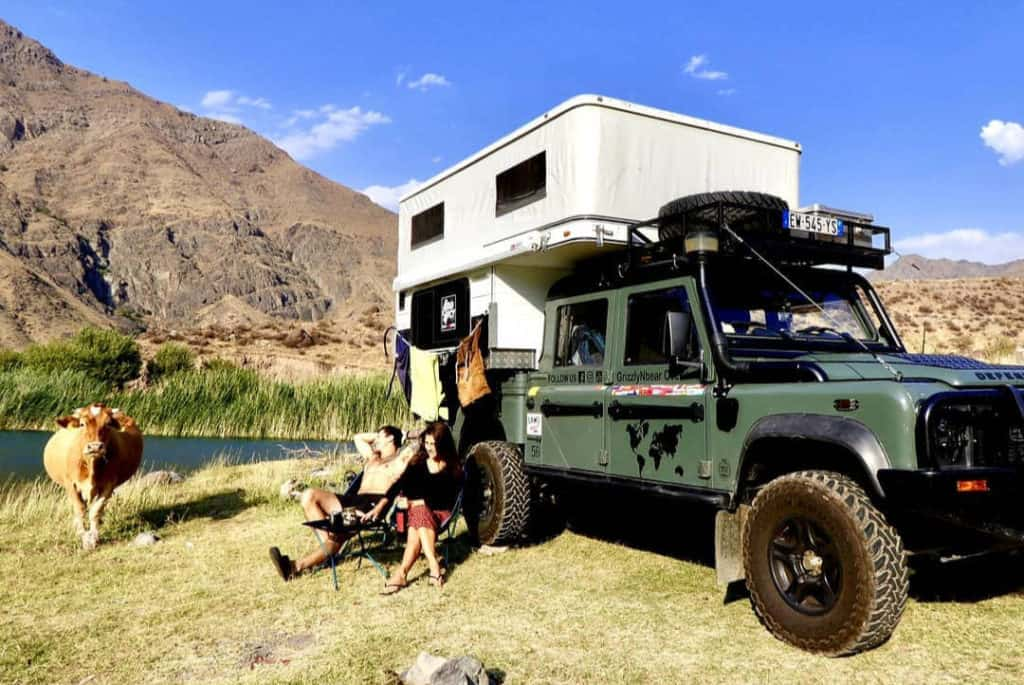 Leigh and Steph sitting by their overland truck camper