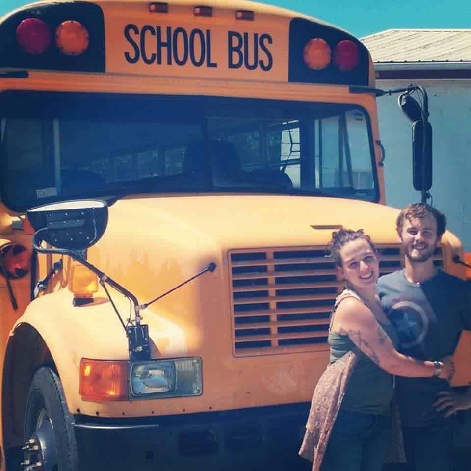 Sumar and her husband standing in front of their brand new school bus camper