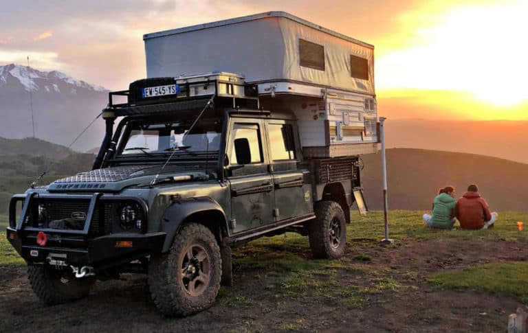 overland camper parked while couple looks at sunet