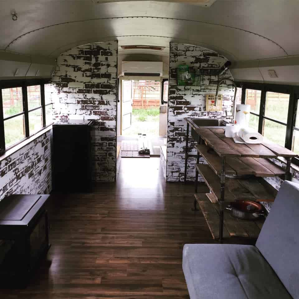 The finished interior of Sumar's school bus camper with wood floors and inlaid brick