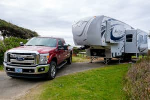 5th wheel trailer and a truck parked at the beach