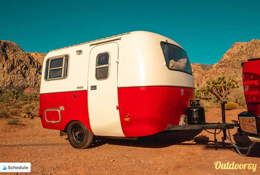 Red and white travel trailer rental parked in the desert
