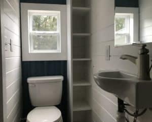Toilet beside floor to ceiling shelving