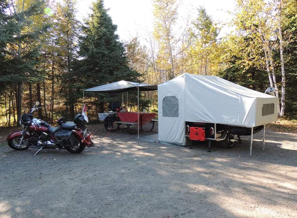 Queen Size Roadman motorcycle pop up Camper set up in the forest with a motorcycle nearby
