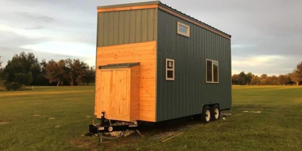 Wood and metal tall tiny home on wheels.