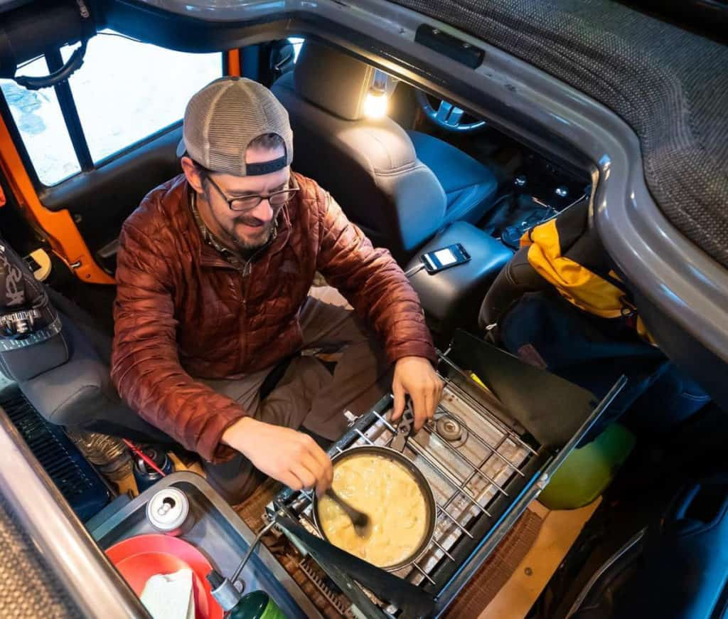 Chris cooking dinner inside his Jeep camper