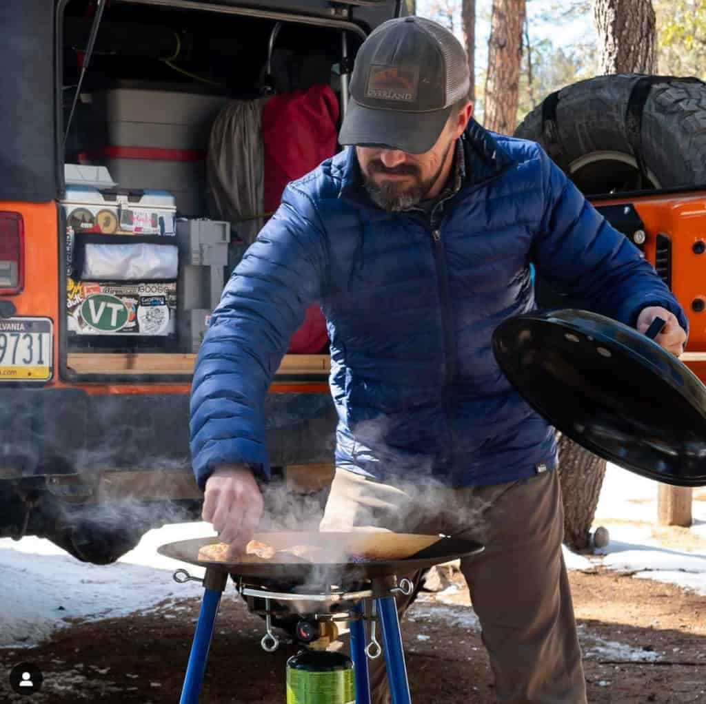 Cooking on a hot grill outside his Jeep Camper