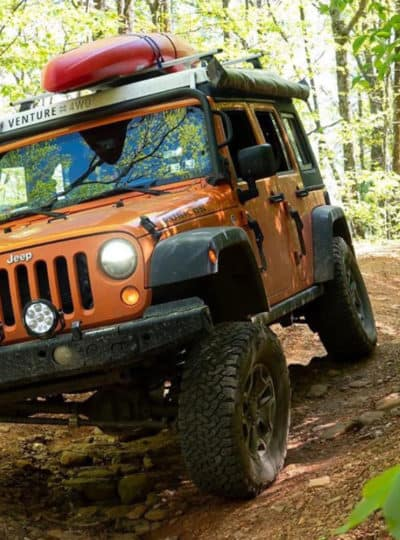 Bright orange Jeep camper overlanding in a forest