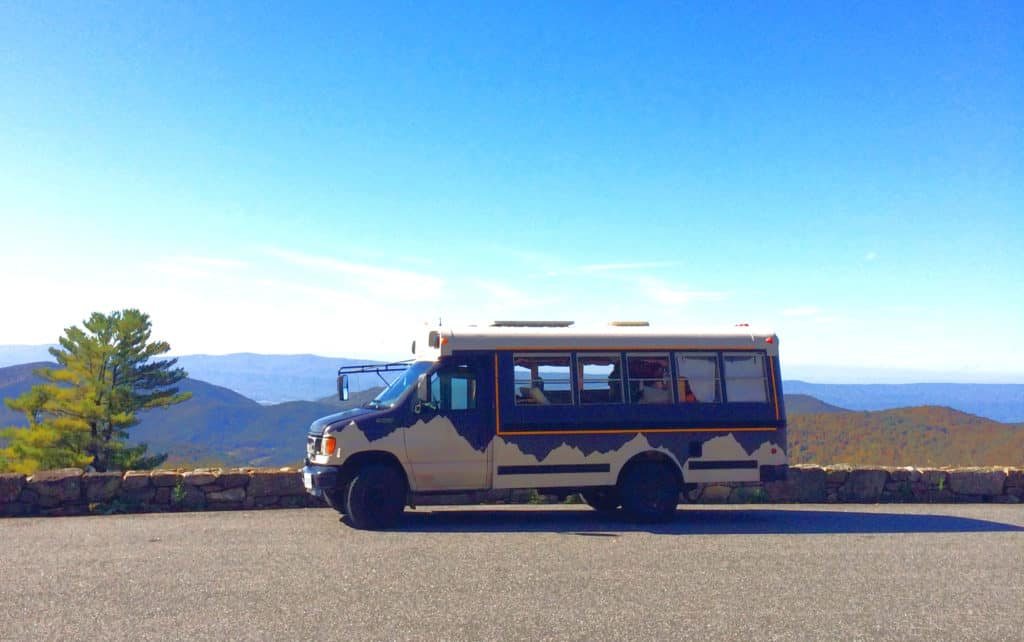 Jane's purple schoolbus with white mountains parked on the road