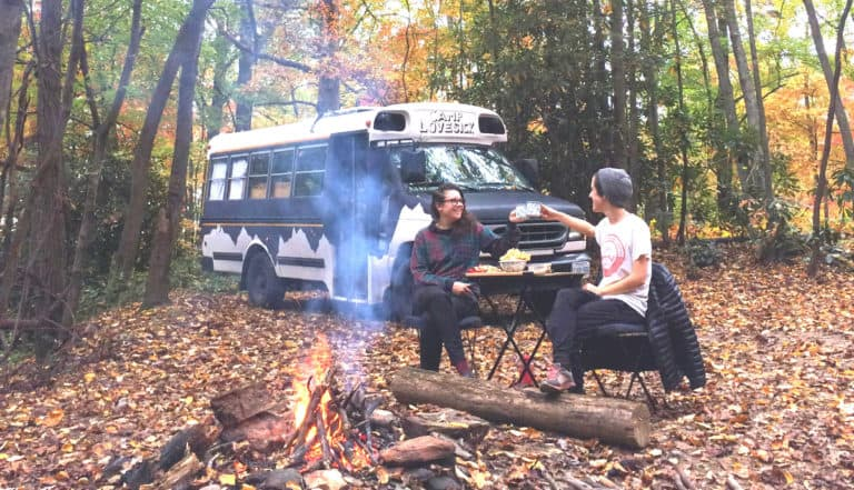 Jane and her wife sitting in front of their purple school bus camper