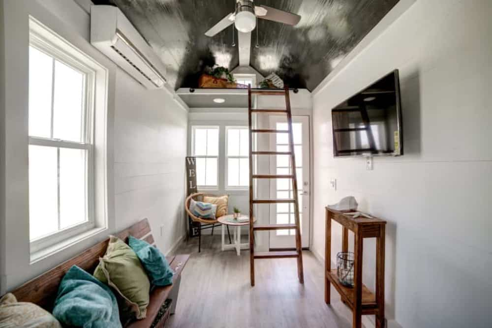 Tiny home interior with a ladder leads up to a storage loft.