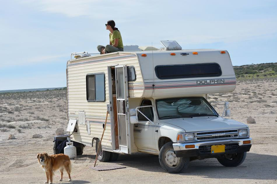 Brittany sitting on top of her Toyota Dolphin Class C RV on the beach